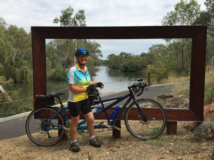 Bronwyn with tandem bicycle with a super sized picture frame and the Murray River and banks behind.