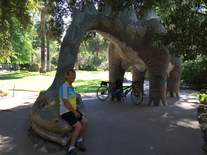 Bronwyn sitting on a dinosaurs nose at the Albury Botanic Gardens Children's area.