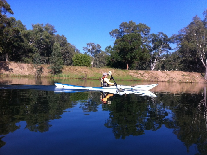 Bronwyn kayaking steadily down the glassy flat water of the Murray.