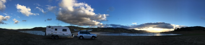 Next morning the van is parked beside the water. The rising sun reflects in Lake Hume and high lights fluffy clouds.