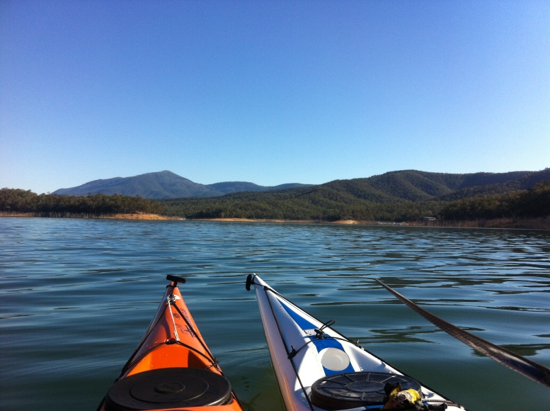 A peaceful view of the kayak bows with the shore and green and blue hills in the distance.