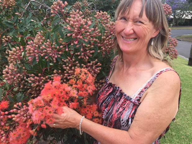 Bronwyn with diamond and silver ear drops and bracelet, with flowering gum tree.
